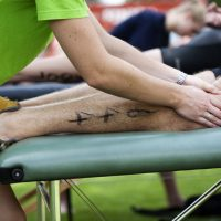 An athlete receiving a leg massage from a physiotherapist.