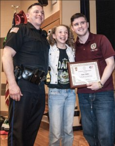 INAUGURAL HONOR: DARE Officer William Frazier shares a moment with sixth-grader Rose Hansen, winner of the first annual Liam Talbot Award for DARE student participation, and guest speaker Liam Talbot, 17, of Hanson.      Photo by Stephanie Spyropoulos.
