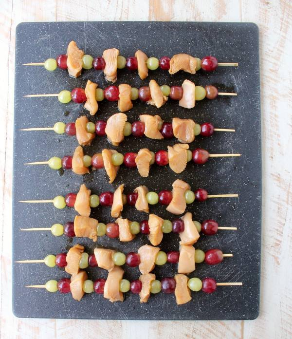 Skewers of marinated chicken & grapes are served with creamy peanut sauce in this Peanut Butter and Jelly Chicken Skewer recipe that's both fun & delicious!