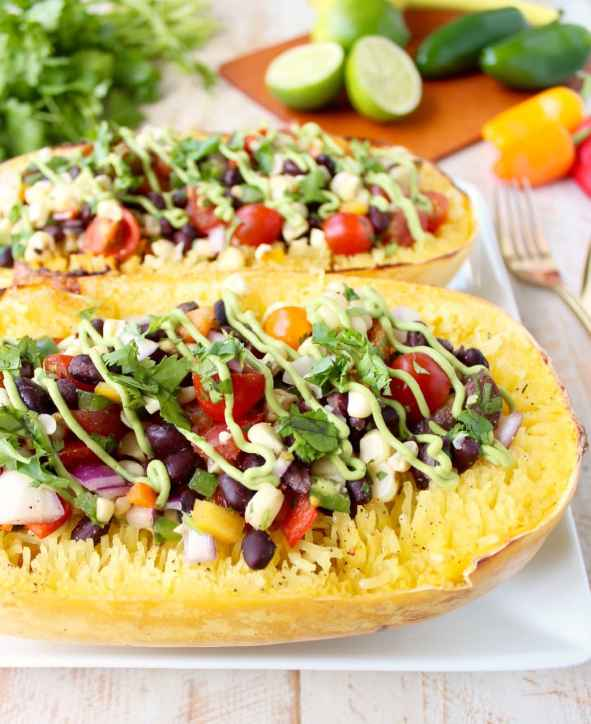 This Mexican Stuffed Squash recipe combines roasted spaghetti squash with black bean corn relish & avocado dressing for a simple vegan & gluten free meal!