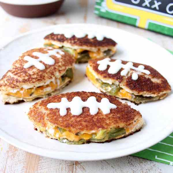 This grilled cheese sandwich recipe is filled with all of the ingredients that make a delicious jalapeño popper, cut into football shapes for game day!