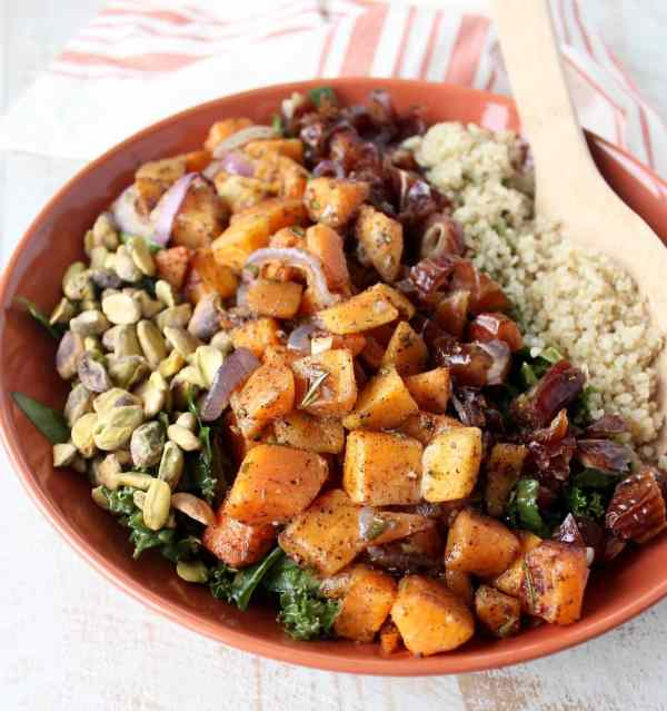 Spinach & kale are tossed with an avocado vinaigrette, roasted butternut squash, pistachios, dates & quinoa in this vegan & gluten free kale salad recipe.
