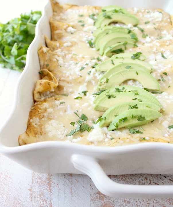 The best vegetarian enchiladas ever combine two cheeses, corn & deliciously creamy avocado sauce for a mouth watering meatless Mexican recipe!