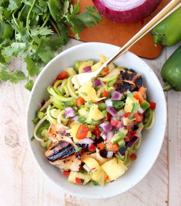 Grilled chicken teriyaki is served over zucchini noodles and topped with pineapple salsa in these healthy, gluten free and delicious zoodle bowls!