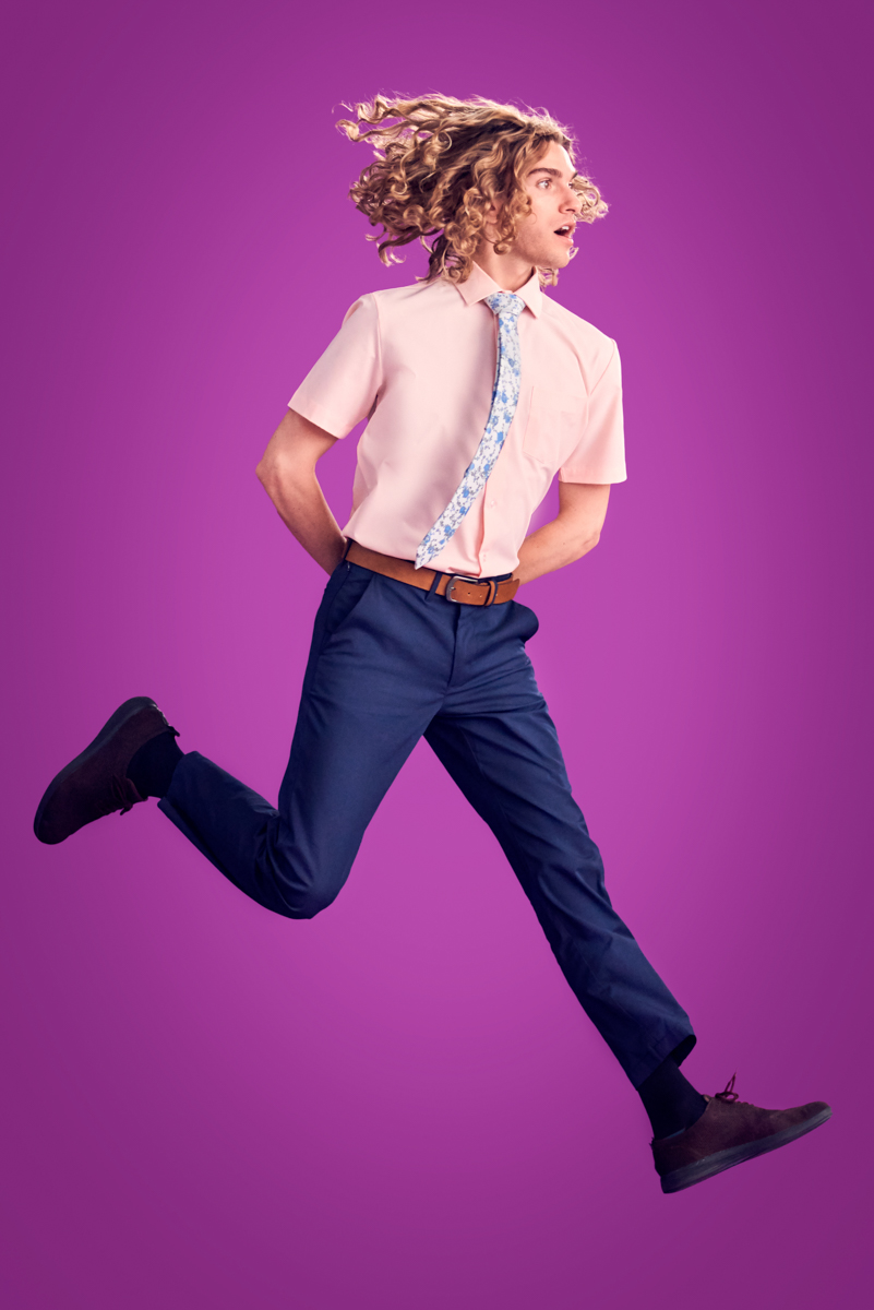 colorful fashion photography bright purple background with male model jumping with curly hair