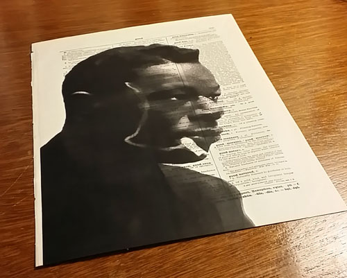 A photo of Nat King Cole printed on a vintage dictionary page from 1897
