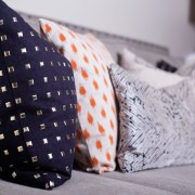 neutral living room | gray nailhead sofa | gold studs pillow | white fur pillow | neutral with pop of orange | britt smith photography