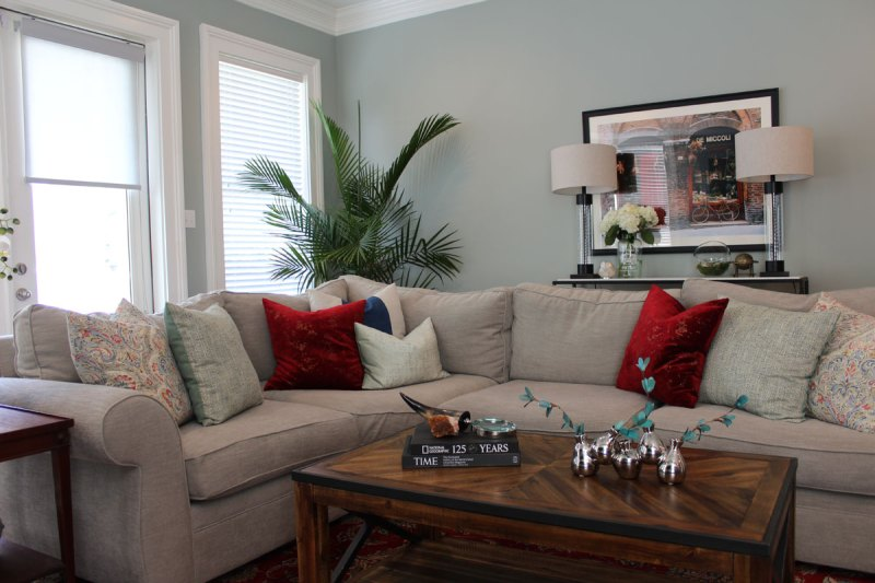 red and blue transitional living room | whitney j decor | new orleans homes | nola decor | red pillows | green walls | sherwin williams oyster gray on the walls | vintage red rug | pottery barn sectional | convertible coffee table | new orleans interior designer | new orleans decorator | new orleans blogger | nola interior designer | nola decorator | nola blogger