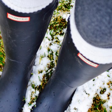 Black hunter boots in the snow with tall white socks and grey leggings.