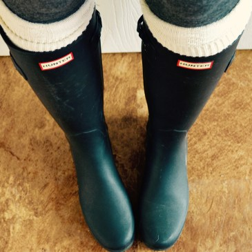 Black hunter boots with white tall socks underneath for warmth.