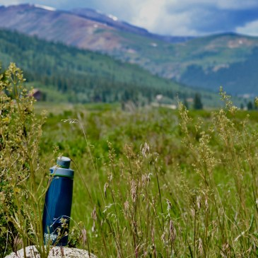 A blue water bottle Camelbak Chute is sitting on a rock in the middle of the Colorado wilderness.