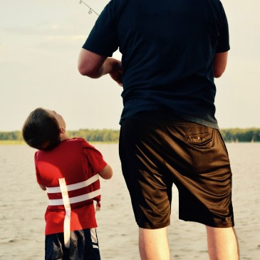 A dad fishing for catfish on a lake while his son wearing a life jacket watches next to him.