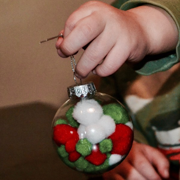 A little toddler hand up close holding his finished clear Christmas ornament with red, green, and white pom poms inside.