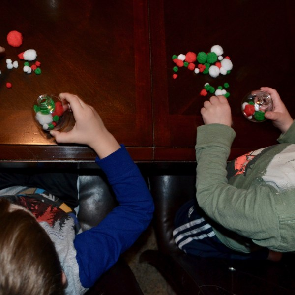 Two toddler boys filling clear plastic ball Christmas ornaments with red, green, and white pom poms.