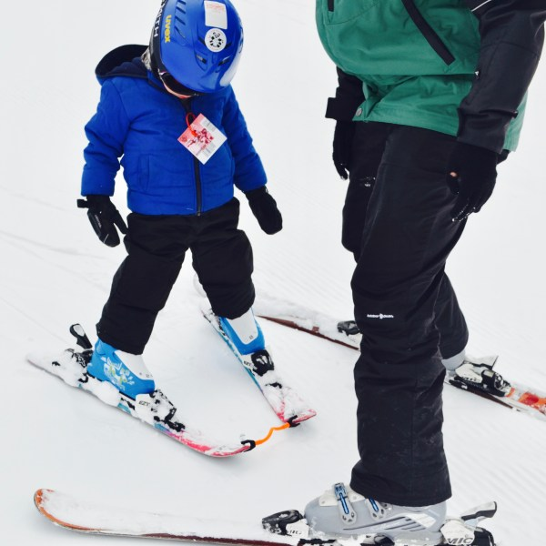 Little toddler learning how to ski and pizza to stop from his instructor at Ski Cooper in Leadville, Colorado.
