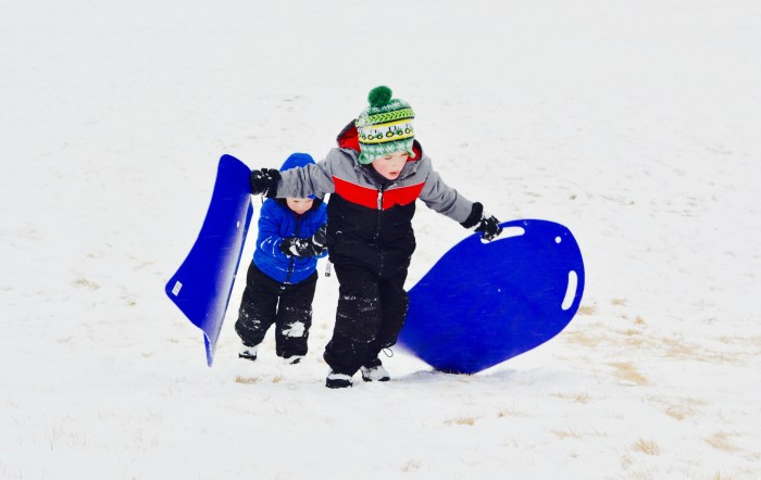 Two young boys carry their blue sleds back up a snowy sled hill.