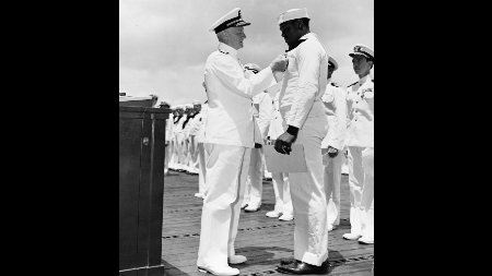 In this file photo taken May 27, 1942, Adm. Chester Nimitz awards the Navy Cross medal to Mess Attendant 2nd Class Doris Miller for his actions aboard the battleship USS West Virginia (BB-48) during the Dec. 7, 1941 Japanese attack on Pearl Harbor. The award was presented to Miller aboard the aircraft carrier USS Enterprise (CV-6) during a ceremony in Pearl Harbor, Hawaii.