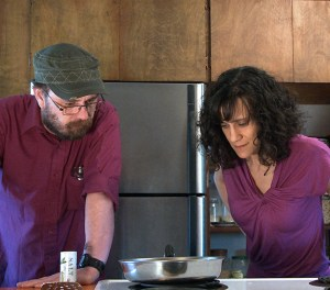 Cheryl and Bill stand at the stove staring intently at a saucepan, waiting for something to happen.