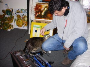 Alex Kitty tastes some cable as Esteban crouches on the floor and sets up to record at Kris Haas's studio. He is surrounded by paintings.