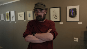 Bill is in a burgandy t-shirt and green hat. He stands, arms folded in front of him, looking at the camera. His framed art of charcoal sketches of human figures are behind him.