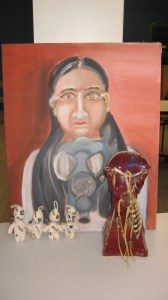 An earth toned painting of a dark-skinned woman with glasses and long hair holding a gas mask in front of her. She looks solemn. Four small soft sculptures of white knitted yarn that are somewhat human shaped. They are covered in surgical stitches and each have one button eye hanging off. A burgandy glazed ceramic sculpture with a dream catcher and feathers.