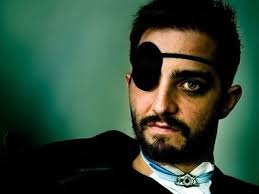 A man with a beard, dark hair, a black eye patch, and a tracheostomy looks at the camera.