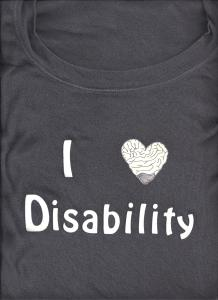 "A gray t-shirt with iron on letters spelling ""I heart Disability."" The heart is drawn like a brain in the shape of a heart."