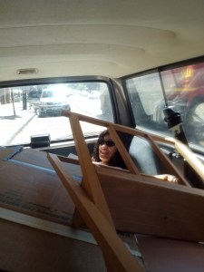 Cheryl, wearing sunglasses, is lying in the back of a station wagon trunk underneath a large pile of paintings.