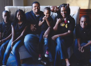 A professional family portrait of Morénike Giwa Onaiwu, her husband, and  their children. They all wear dark t-shirts and blue jeans. Smiles range from serene to exuberant.