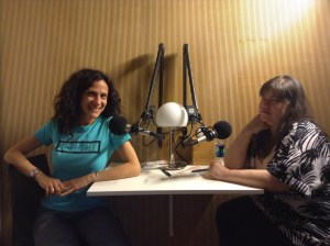 Two women sit at a table with studio microphones in front of them. Cheryl wears a Criptiques t-shirt, and Lavaun wears a black and white dress.