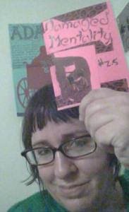 "A woman with glasses holds up a small, pink zine ""Damaged Mentality #2.5"""