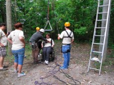 A man in a wheelchair is strapped into a safety harness getting ready for the zip line in the woods.