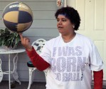 "Dani spins a basketball on her finger and wears a t-shirt with ""I was born to ball"""