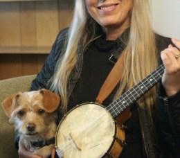 A small, scruffy, apricot-colored terrier sits next to a blond smiling woman. She holds a banjolele.