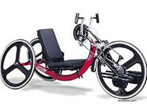 A red three-wheeled cycle, low to the ground. Pedals are attached to the front wheel and are operated by hand.