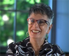 Sue Perlgut smiles broadly in a portrait. She is an older white woman with short hair and glasses.