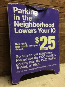 "A purple Portland Community College sandwich board sign with white and yellow lettering leans against a brick wall. It reads: ""Parking in the neighborhood lowers your IQ. Not really. But it will cost you a ticket. $25. Ouch. Be nice to our neighbors. Please use the PCC overflow parking lots, the PCC shuttle, TriMet, or Bike. Find info on the Parking and Transportation Services web site."""