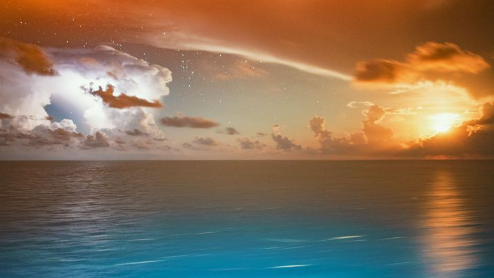Lightning strikes as the moon rises over the Caribbean Sea