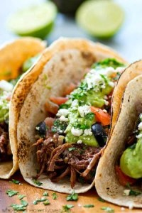 Kicked up chipotle crockpot beef tacos piled high with a fresh greek salsa and the most amazing avocado crema ever! Meet your new favorite taco.