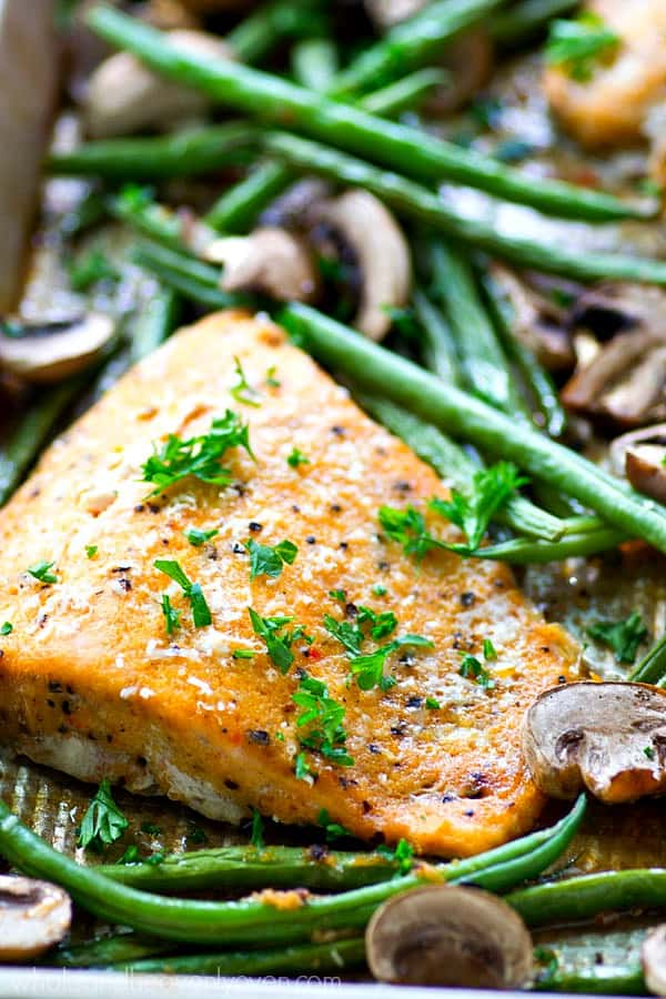 Roasted in a flavorful lemon garlic Parmesan sauce and lots of little mushrooms and green beans, this baked salmon is a breeze to throw together for a weeknight dinner and is packed with SO many amazing flavors!