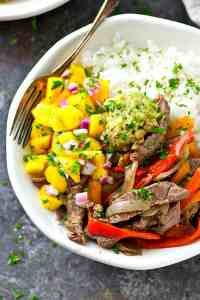 Flavorful steak and peppers in easy loaded rice bowls form! These colorful rice bowls are heaped high with tons of beef and an insanely-flavorful mango pico de gallo!