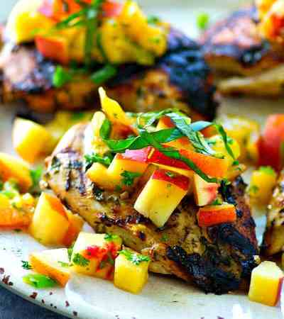 This juicy grilled chicken is marinated in the most flavorful basil sauce and a fresh peach salsa piled on top brings out all the best summer flavors! --- Let the chicken slowly marinate overnight for the best results.