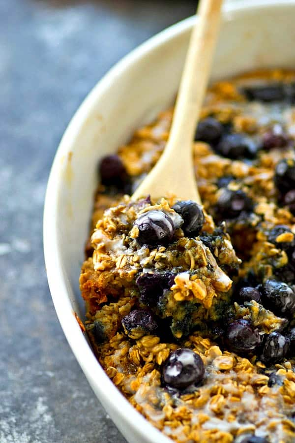 This easy and energy-packed baked oatmeal is loaded full of blueberry muffin goodness and covered in a sweet vanilla glaze. Enjoy it with milk or straight outta the pan!