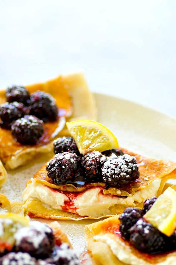 Flaky melt-in-your-mouth crepes are stuffed with a tangy lemon cream cheese and topped with a fresh blackberry sauce.---these blackberry lemon cream cheese crepes are a brunch must!