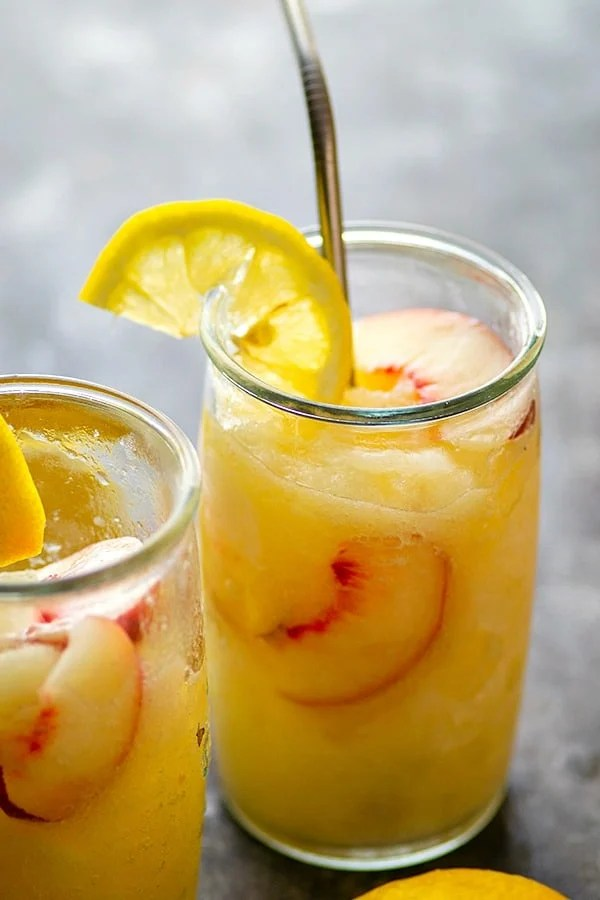 Frozen Peach Rum Lemonade Slushies - Sweet, tangy, and loaded with summer peach flavors, these frozen peach rum lemonade slushies are summer sippers taken to the next level!