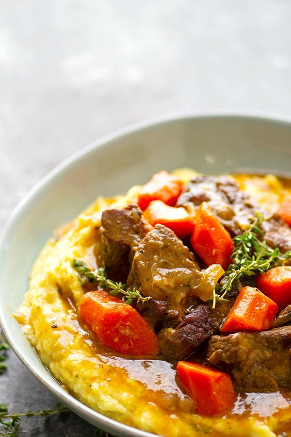 Stout-Braised Beef Short Ribs - Saucy and incredibly tender stout-braised beef short ribs are piled high over creamy bowls of mascarpone polenta for the ultimate AND surprisingly easy cold weather comfort food!