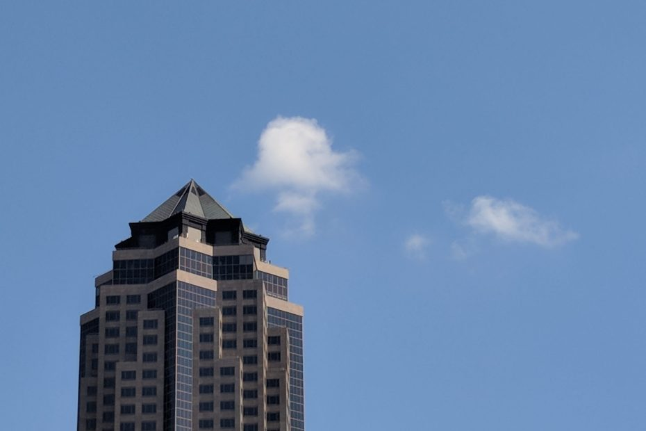 Top of 801 Grand against a blue sky and tiny clouds