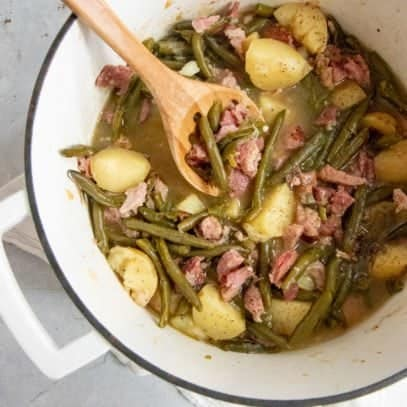 Southern Style Green Beans and Potatoes in a white Dutch oven, with a wooden spoon