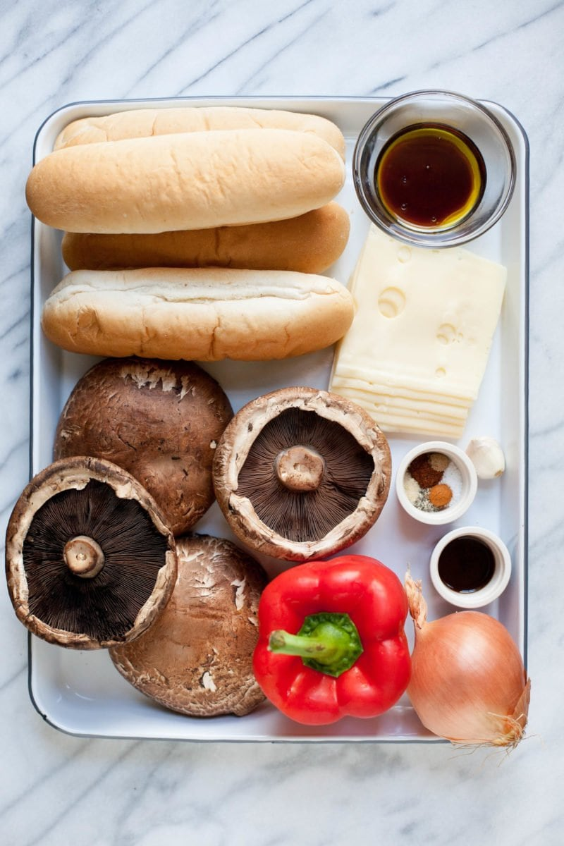 Overhead shot of ingredients for portabella cheesesteaks - portabella mushrooms, red pepper, onion, Swiss cheese, hoagie buns