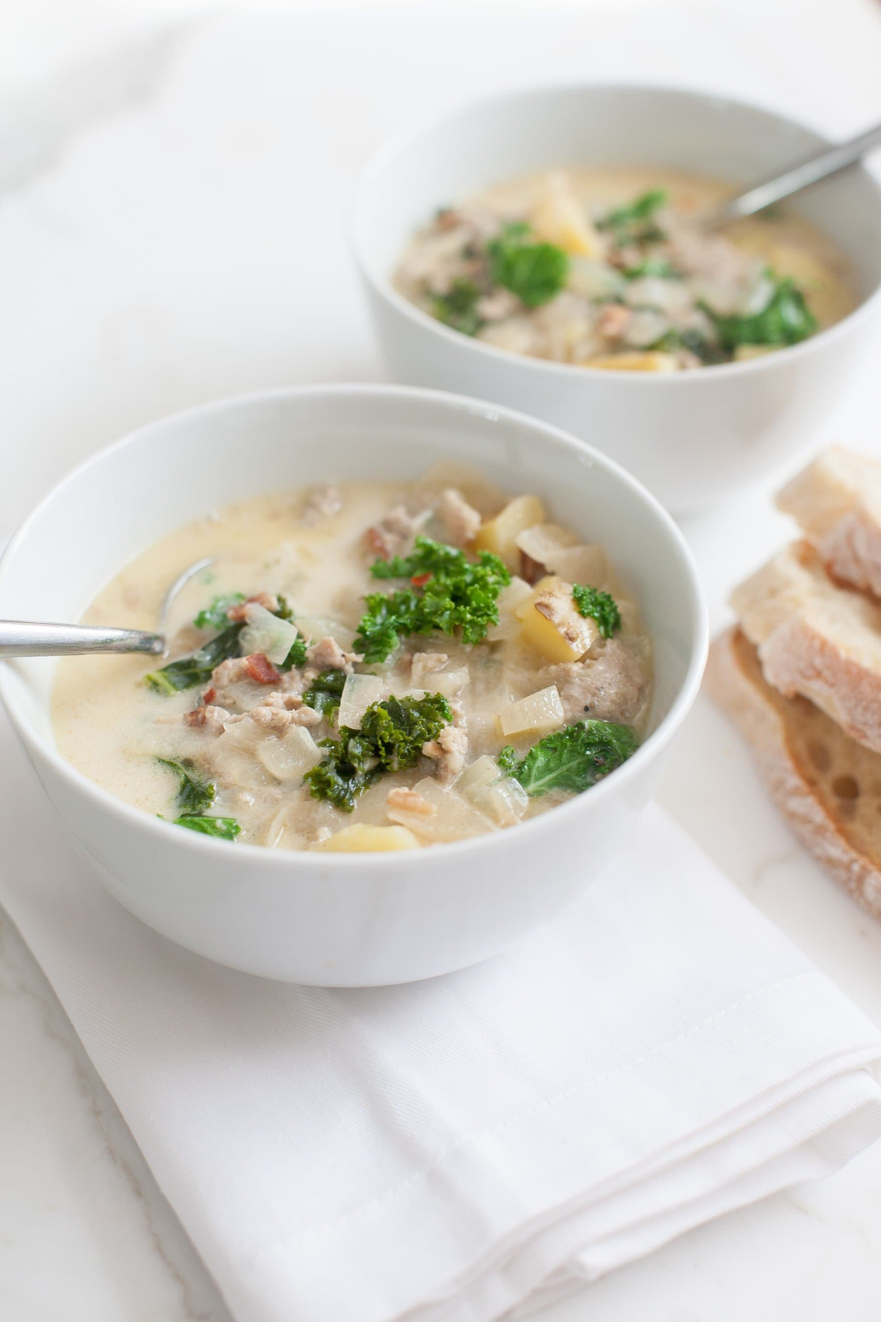 Two bowls of zuppa toscana with spoons inside on a marble counter with slices of bread.